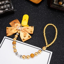 Купить с кэшбэком MIYOCAR Bling golden rhinestone bow gold beads Luxurious dummy clip holder pacifier clips holder/Teethers clip pacifier chain