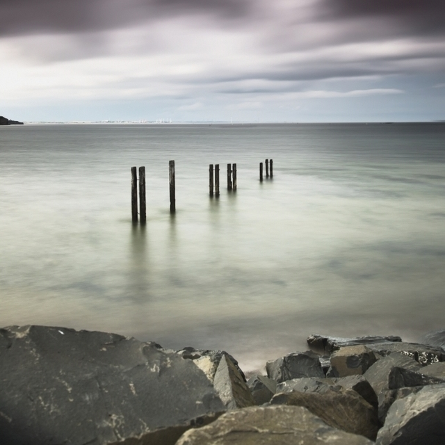 Wooden posts in a row in the shallow water along the coast under dark storm clouds;St mary's bay northumberland england