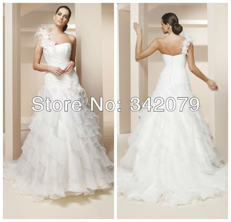 4f4d9b299c3 ph10674 One shoulder organza and tulle trumpet bridal gown Large floral  accent on the side of hip peacock feather wedding dress