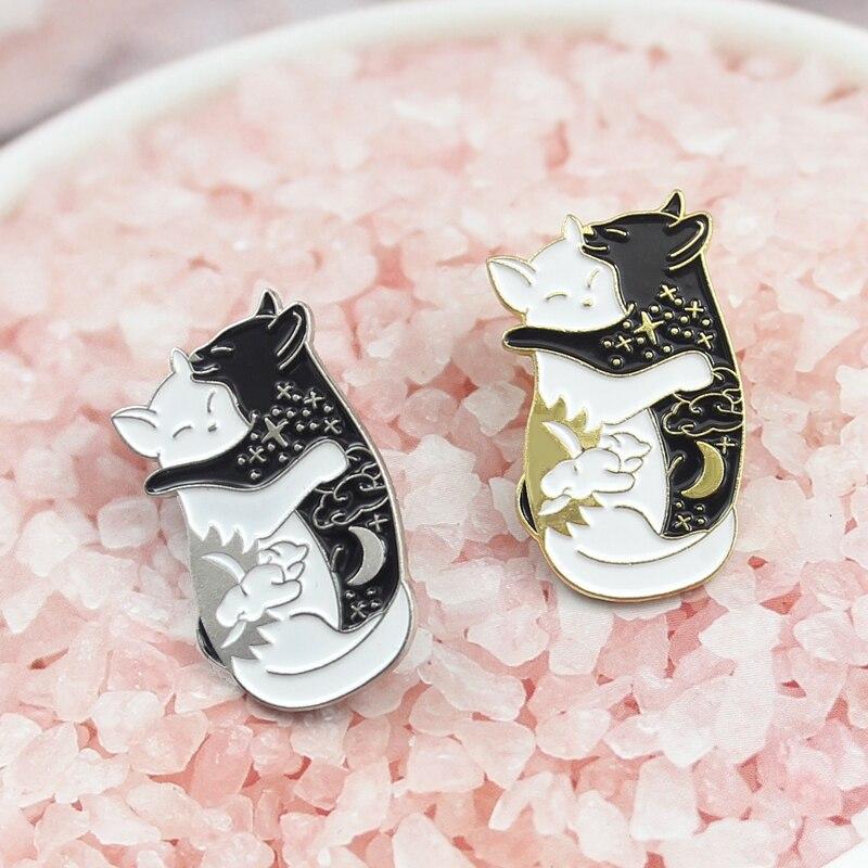 Un paio di simpatici gatti bianchi e neri si stringono lun laltro dormendo spilla stelle luna vestire romantiche manda amante