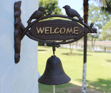 European American rural countryside vintage wrought iron doors welcom doorbell ringing bells in front of mural