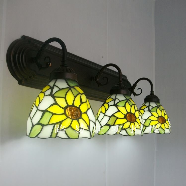 To three elongated European pastoral Wall Lamp of yellow sunflowers Tiffany lamps. Backdrop balcony Lighting restaurant table