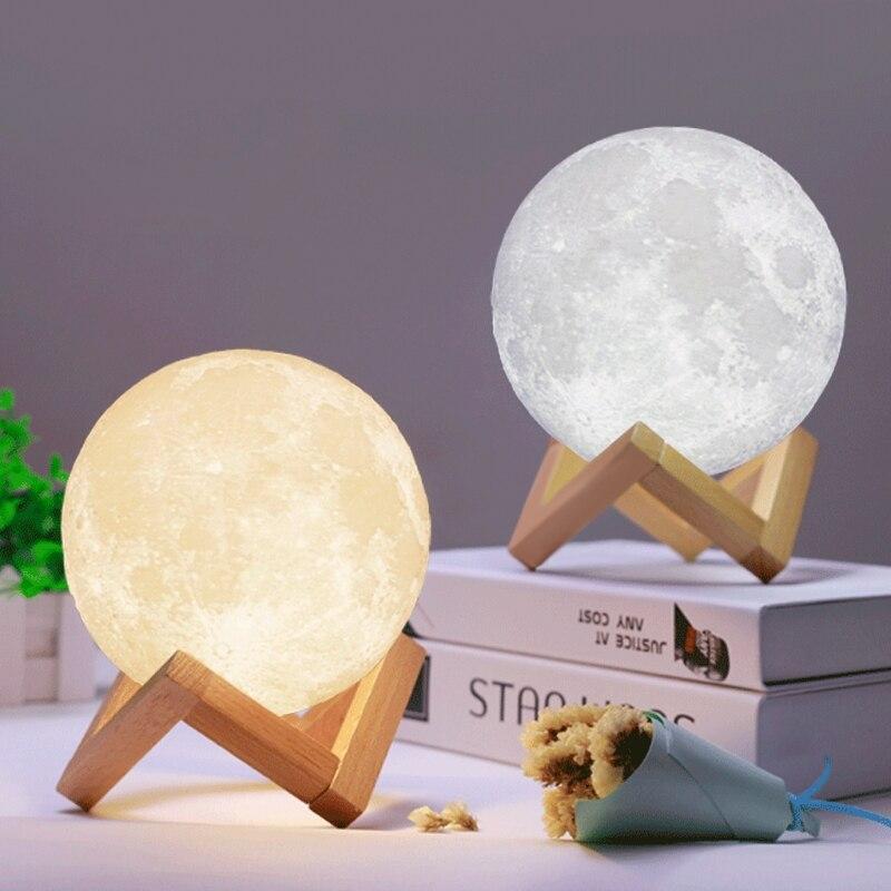 שתי מנורות ירח על בסיסי עץ בצבע כסוף וצהוב