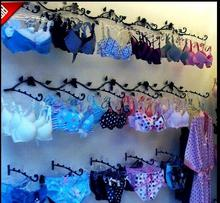 The iron art garment bra shows a wall hook hanging in clothing store