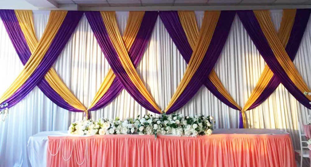 White Wedding Backdrop With Gold And Purple Swags And Drapes