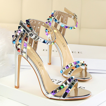 все цены на Roman style women shoes 2019new European and American fashion stiletto super high heel toe word with hollow color rivets sandals онлайн