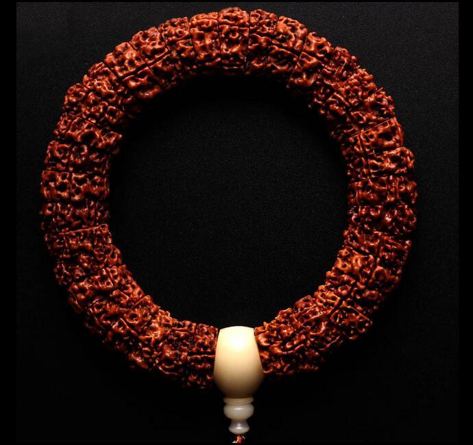 Bodhi hand holding red prayer beads bracelet