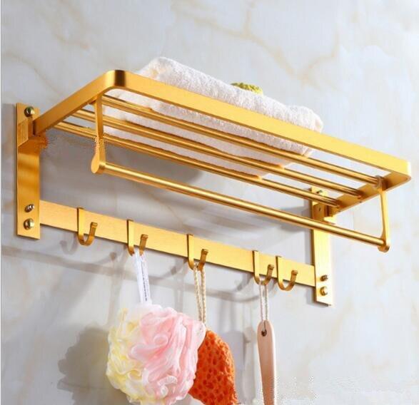 Zlatý skládací věšák na ručníky v koupelně