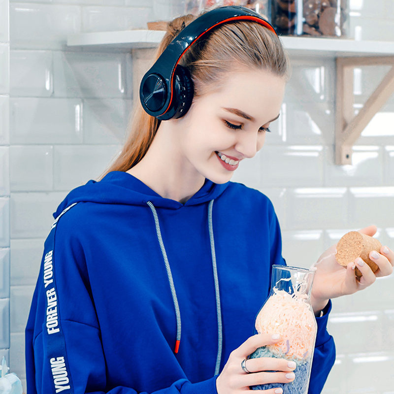 Foto on women's head Wireless foldable headphones with mic. Foldable wireless earphones for mp3