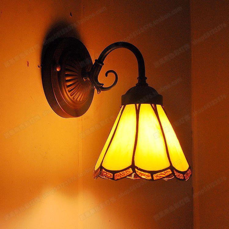 """Tiesioginis gamyklos žemyninis balkonas """"Tiffanylamps"""" prieš veidrodį. Retrospektyvios mažos sieninės lempos miegamojo lovos miegamojoje"""