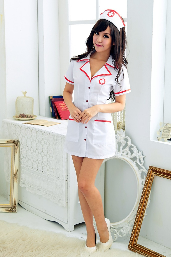 Sexy young brunette female nurse with stethoscope in scrubs stock photo