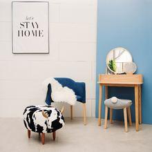 Корова сидя на пирсе скамейка стул для ног