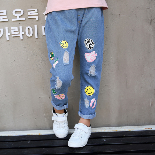 636cf73232 2018 Fashion Hole Big Girls Jeans Trousers Cartoon Smiling Face Printed  Pattern Kids Pants Girls Denim Pants Children Clothing
