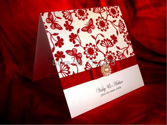 white wedding invitation with red ribbon