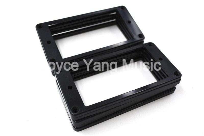 Der schwarze Humbucker Rahmen Pickup Rahmen umgibt Ringe für