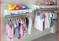 High end women's clothing shelves. White wall mounted hangers. Clothing store hangers.005