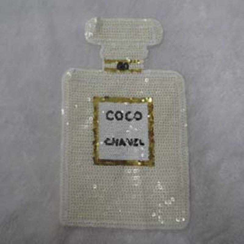 Hímzésvasaló a ruhák divatfoltjainak parfümös flakonjaival