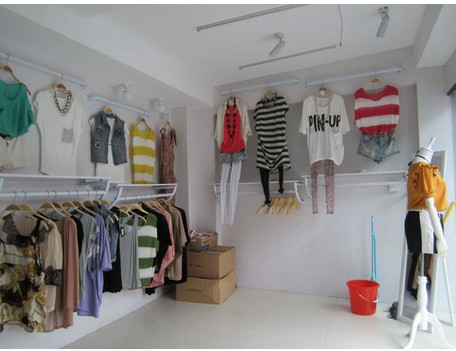 On the wall is hanging shelves display clothing store