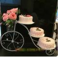 European creative frame, wrought iron cake. Bicycle wedding three layer cake. Flower birthday multilayer dessert