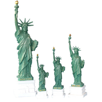 A Statue of liberty sculpture is displayed on living room office book desk as tourist souvenir in New York crafts bookshelf home