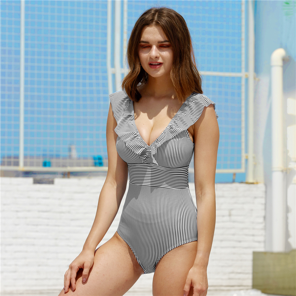 Foto of white/black women's one-piece v-neck swimsuit. Female one-piece swimwear for swimming pool