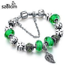 Женский браслет с зелеными бусинами серебряного цвета листьями