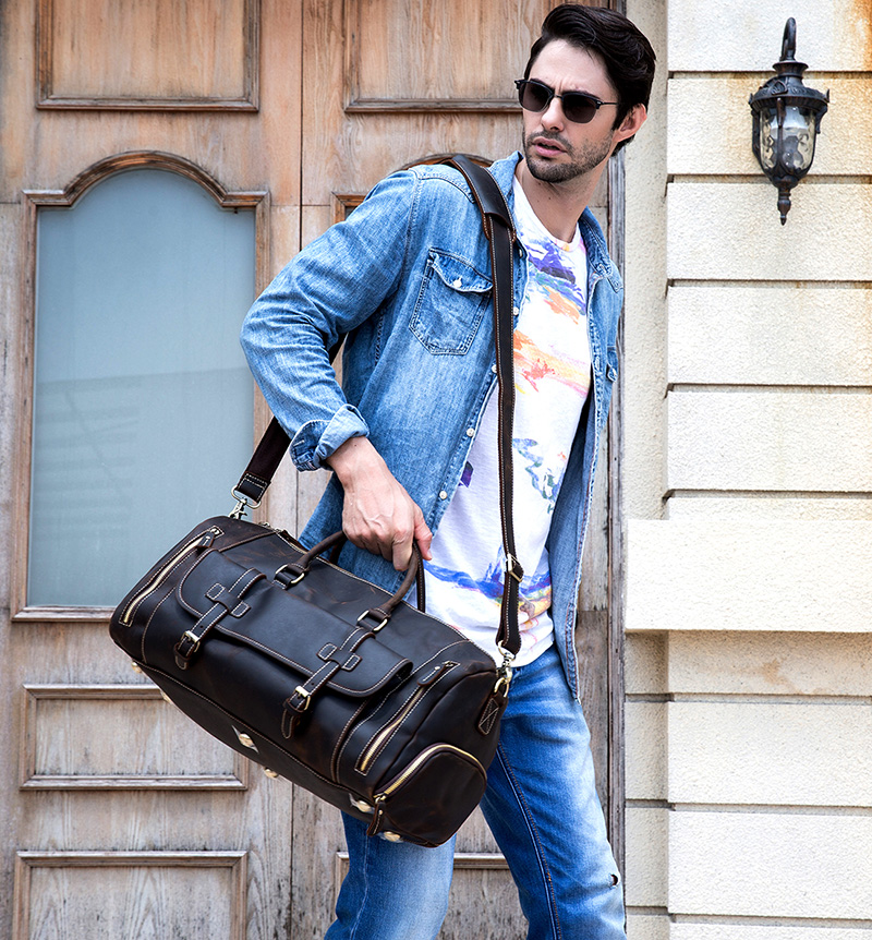 a guy carrying a vintage leather duffle in coffee color on the street