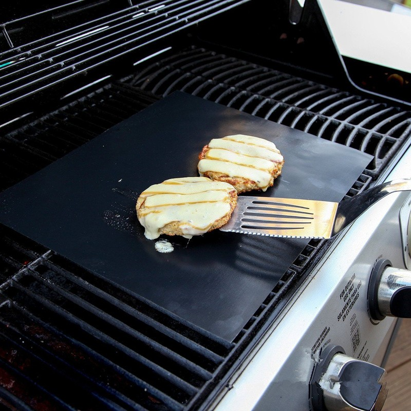 grille burger on top of BBQ grill mat