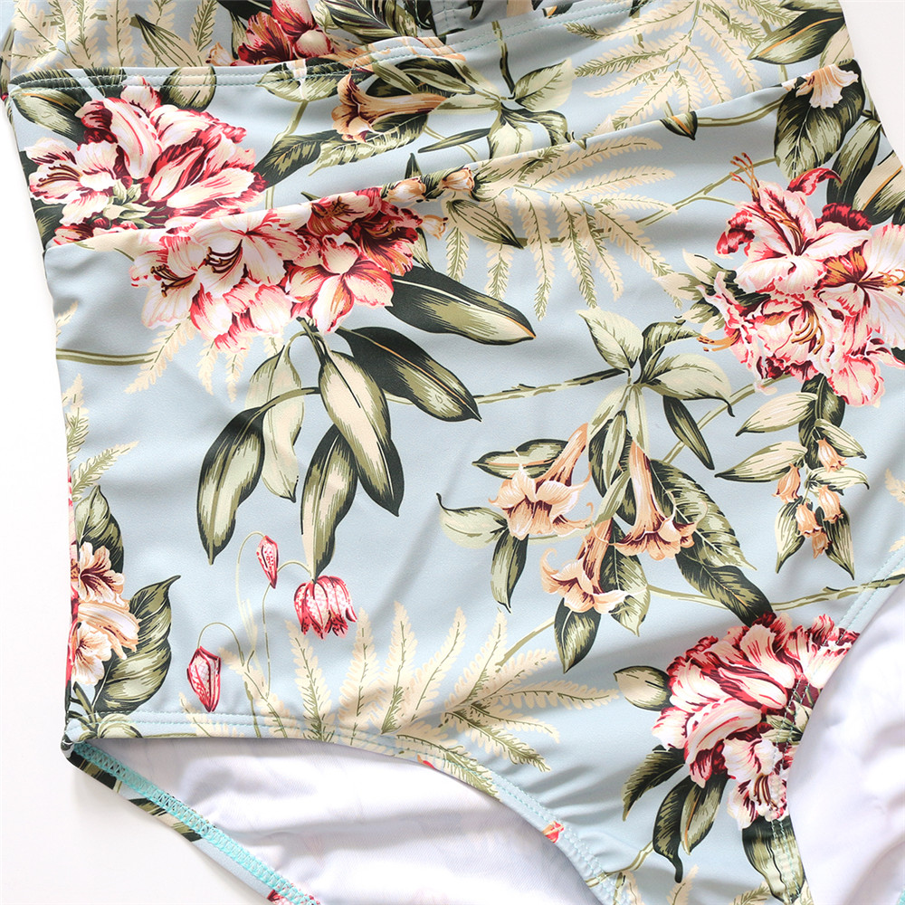 Foto of bottom part of flower print from the top women's one-piece v-neck swimsuit. Female one-piece swimwear for swimming pool
