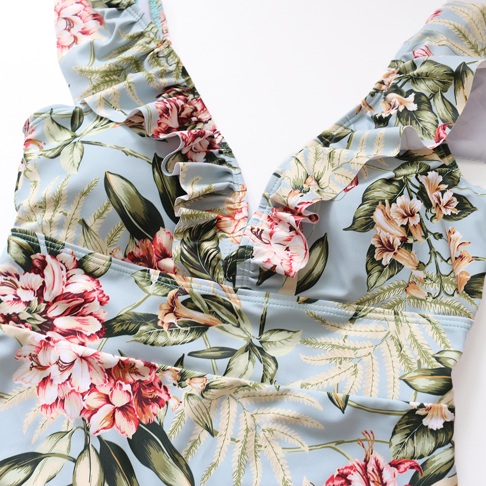 Foto of part of flower print from the top women's one-piece v-neck swimsuit. Female one-piece swimwear for swimming pool