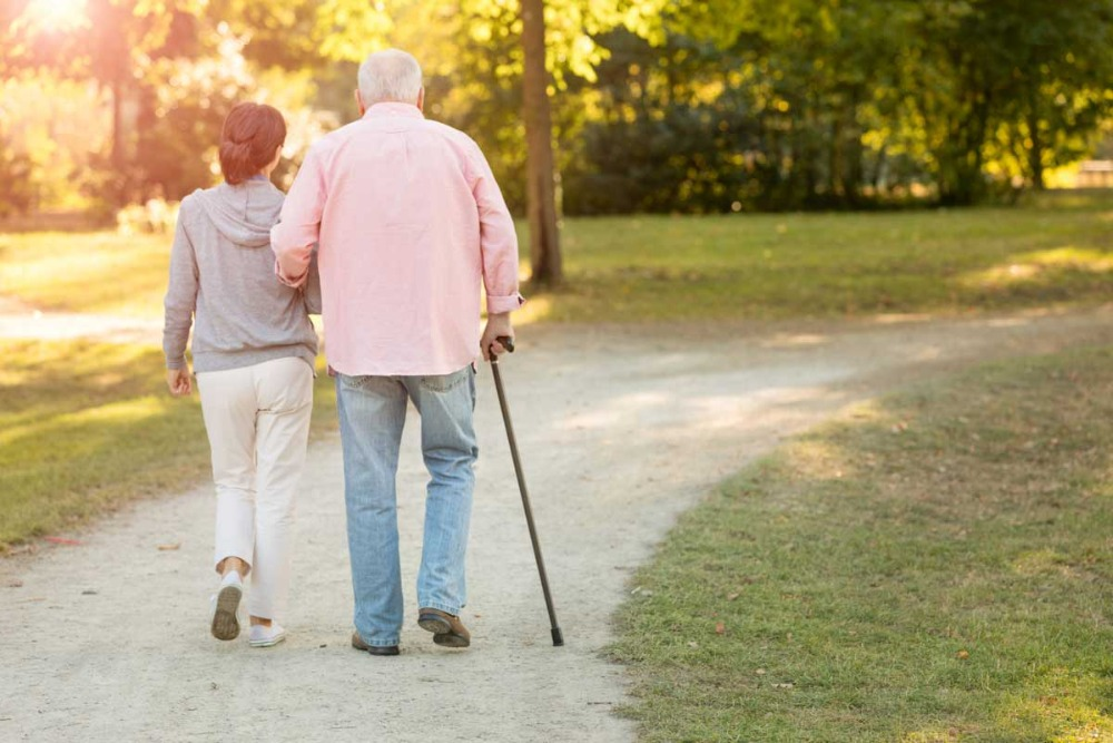 senior-with-cane-walking-with-young-woman