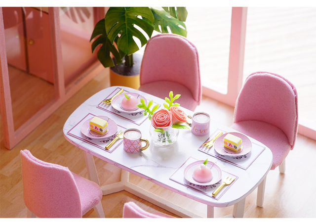 dining room of the pink doll house. table and chairs, the table is set with plates and cutlery