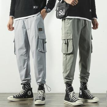 Męskie spodnie bojówki dorywczo spodnie męskie kieszenie biegaczy męskie dorywczo luźne jednokolorowe spodnie męskie japońskie spodnie dresowe męskie tanie i dobre opinie davidyue Cargo pants Mieszkanie Poliester COTTON REGULAR Na co dzień Midweight Suknem Kostki długości spodnie Elastyczny pas