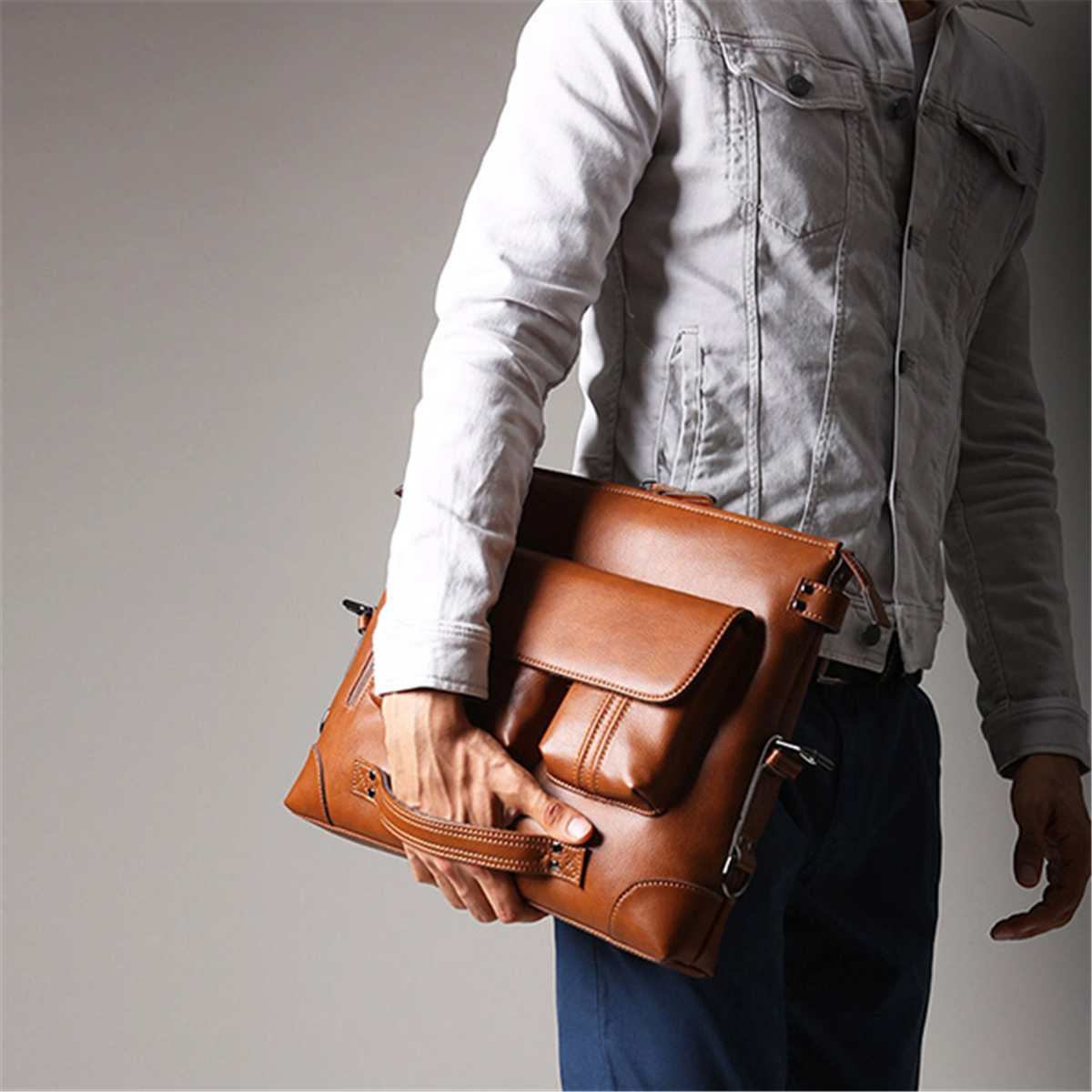 a guy holding a shoulder bag