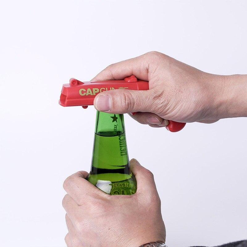 Creativo Flying Cap Launcher apribottiglie apribottiglie a forma di pistola coperchi di bottiglia sparatutto tappo portatile rosso forma di pistola apri strumento Bar 1