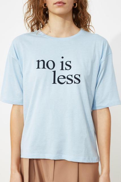 Camiseta de mujer en color celeste holgada y estampada con letras en ingles NO IS LESS.
