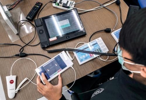 "p50信息科技企业用一项项""黑科技""为一线医疗工作者构筑起一条看不见的""智 慧防线""。图为工作人员在调试护患对讲系统 摄影_ 新华社记者 潘昱龙.jpg"